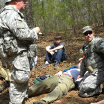 SGT Guy McMillan takes notes as CPL Jason Austin attends to an 'injured' scout during the search and rescue exercise.