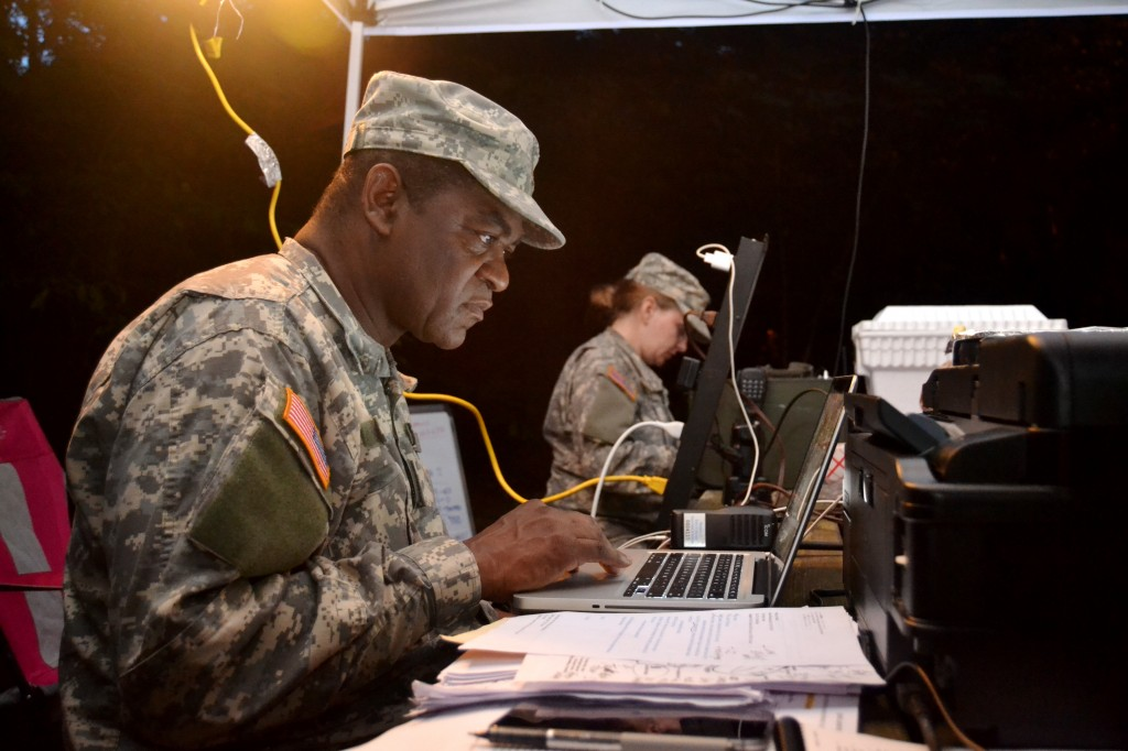 CLARK CREEK SOUTH CAMPGROUND, Acworth, June 5, 2015 – Maj. Herb Jones, the Operations Officer for 1st Brigade, Georgia State Defense Force (GSDF) and acting Incident Commander for Defender Northwest Georgia Field Training Exercise (FTX) 2015, scans over reports and prepares orders for the Soldiers. The FTX tests the capabilities of the Soldiers and staff of the GSDF in their ability to respond to a disaster. (Georgia State Defense Force photo by Master Sgt. Mark D. Woelzlein, Public Affairs Office)