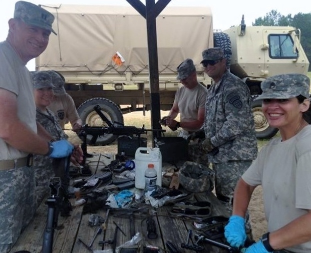 Georgia State Defense Force Soldiers field strip and clean M249 Machine Guns. Pictured left to right: CPT David Bignaught, SGT Christopher Lowry, WO1 Howard Seay, SPC Jon Van Holm, SSG Cindy Dunlap. Photo by PV2 Bernard Cameron