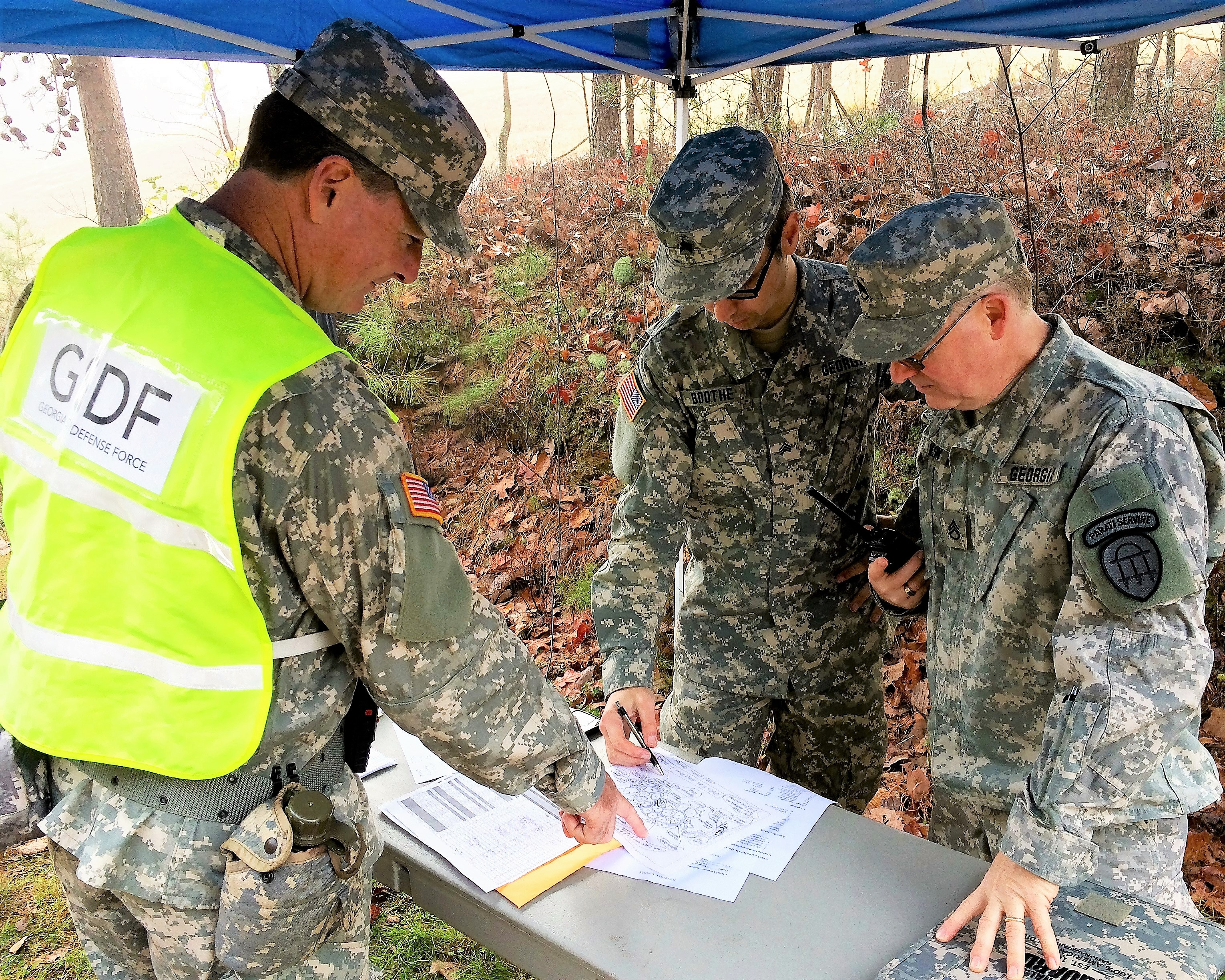 GEORGIA NATIONAL CEMETERY, Canton, Georgia, December 12, 2015 – Sgt. 1st Class Jim Dempsey (left) receives an update from Sgt. Matt Boothe (center) and Staff Sgt. Brian Wilson (right) on the status of traffic control operations during the National Wreaths Across America event. (Georgia State Defense Force photo by Pvt. Michael Chapman, Public Affairs Office)
