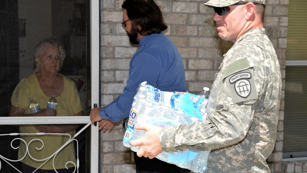 A member of the Georgia State Defense Force delivers water to a resident of Ludowici, Georgia in the aftermath of Hurricane Matthew on October 9, 2016. (Georgia State Defense Force photo by Sgt. 1st Class Alasa)