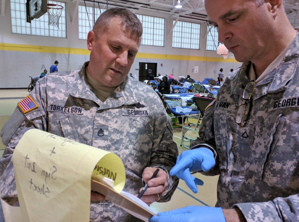 Staff Sgt. Torkelson (left) and Pfc. Lyman (right) review a task list in the hurricane evacuation shelter at Tubman Education Center in Augusta, Georgia on October 9, 2016. (Georgia State Defense Force photo by 2nd Lt. Hughes)