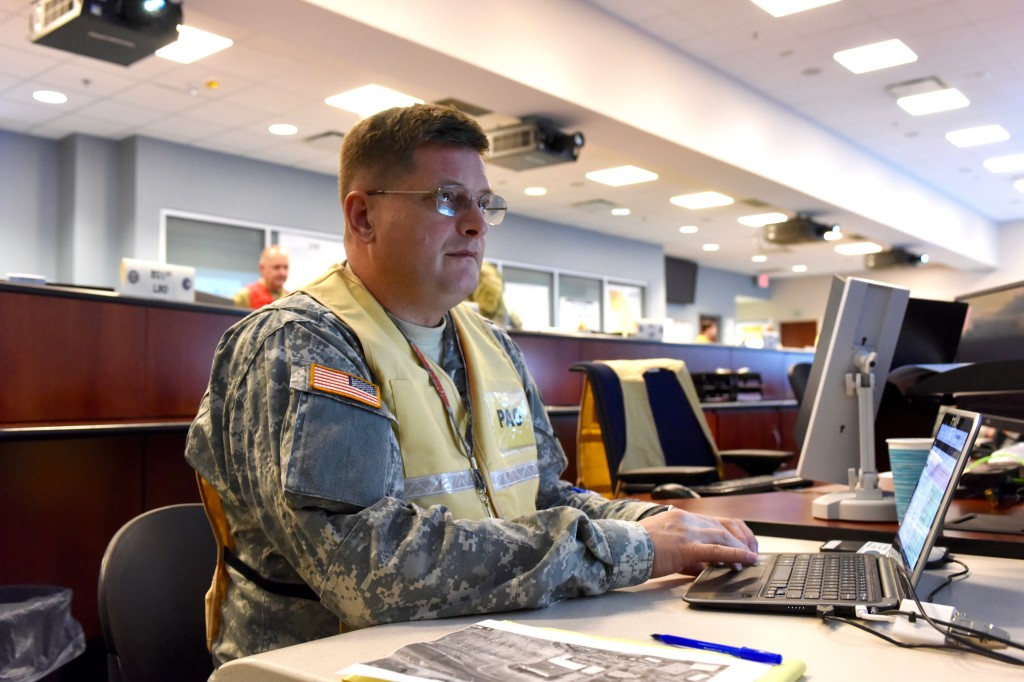 Working in the Joint Operations Center at Clay National Center in Marietta, Georgia, March 27, 2017, Capt. V. Timchenko, GSDF Public Affairs Branch Chief, monitors the display board as he updates the news feed during Vigilant Guard 2017. Georgia State Defense Force photo by Spc. Alexander Davidson