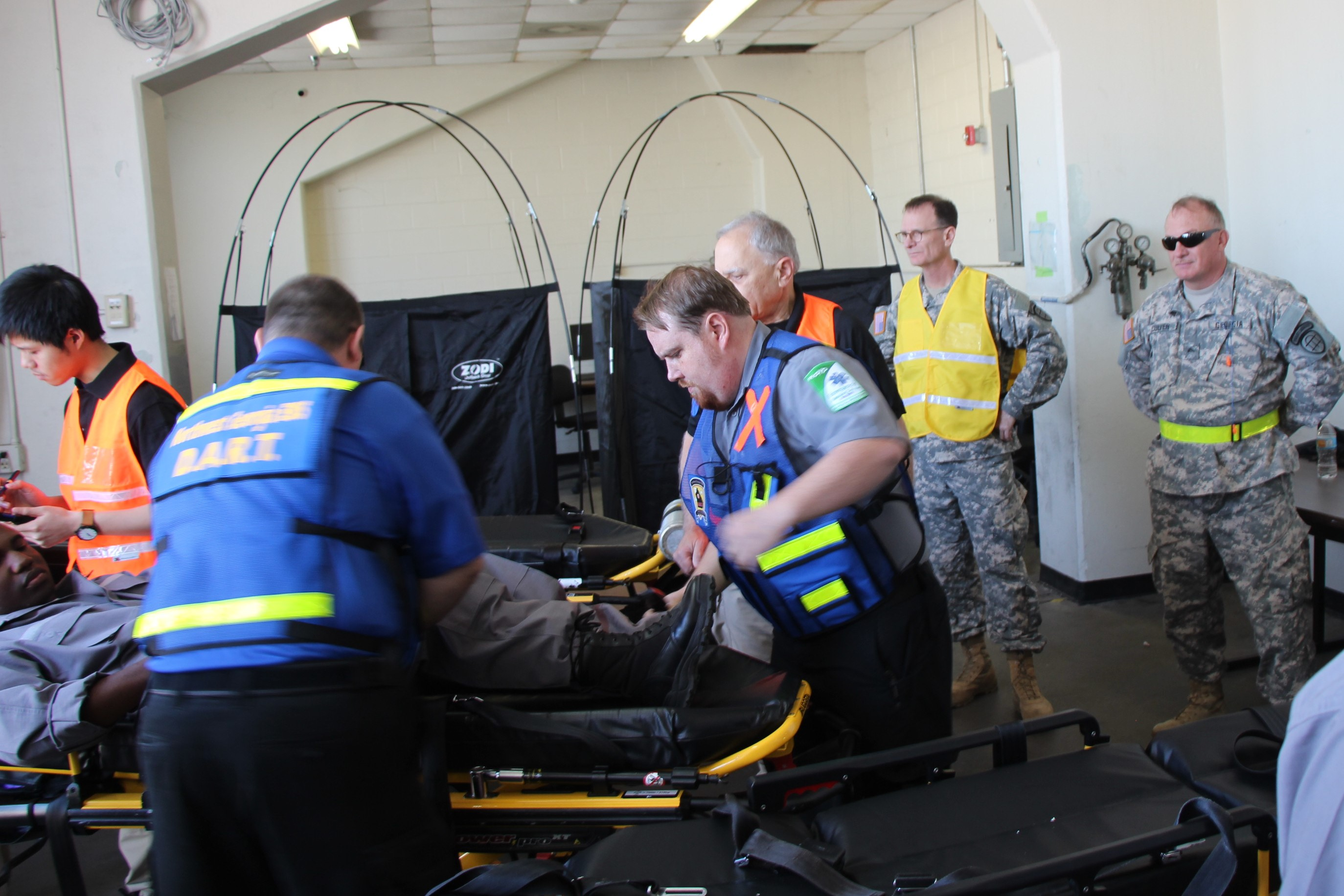 Joint GA State Medical Assessment Team conducts a triage assessment for the victim of the disaster (role player) as GA State Defense Force soldiers are staying nearby ready to assist during the Vigilant Guard 2017 exercise March 29, 2017, at Air Dominance Center in Savannah, GA. Vigilant Guard 2017 Georgia is a multi-state multi-agency training exercise, sponsored by U.S. Northern Command, in collaboration with the National Guard Bureau.  Georgia State Defense Force photo by Capt. Vadim Timchenko.
