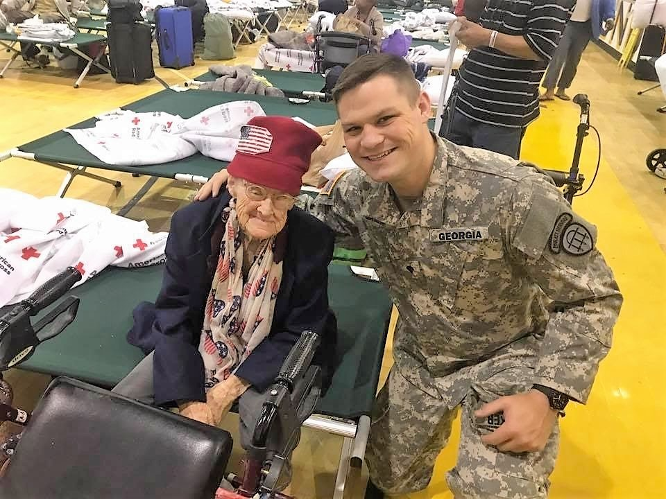 Spc. Nathan Baker with a hurricane evacuee in Augusta, Georgia.