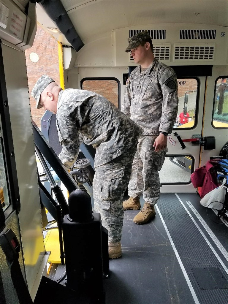 Sgt. Raymond Liles, left, and Spc. Nathan Baker, right, load luggage and other items onto a bus before returning the evacuees to Chatham County. Georgia State Defense Force photo by Sgt. Sandra Ibarra