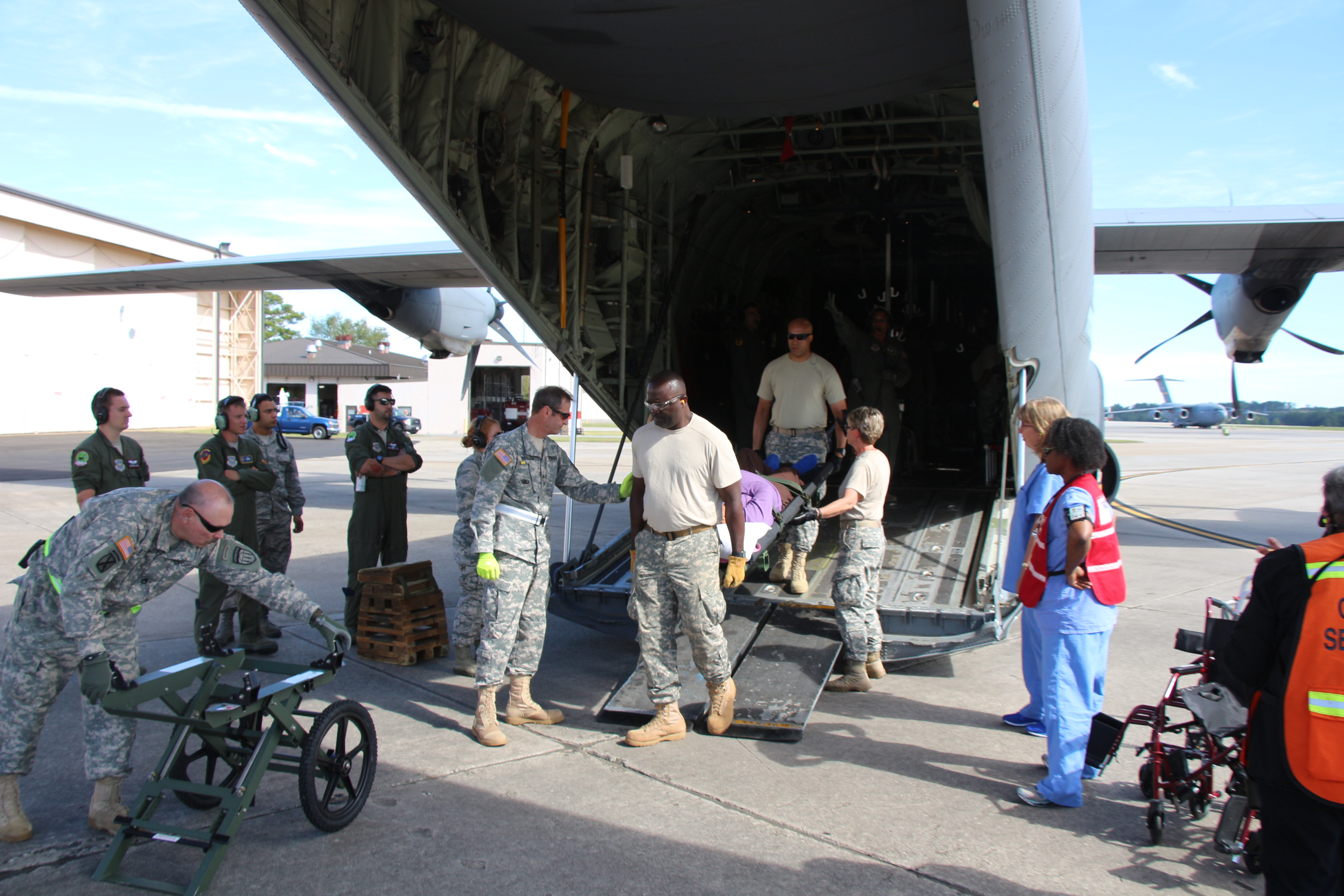On photo: Sergeant First Class Steven Stewart prepares the litter carrier, Lieutenant Colonel Ronald Russell leads the offloading procedure that is conducted by Private Felix Apiki, Staff Sergeant Vicki Anderson and others. Over sixty Georgia State Defense Force soldiers tirelessly worked for ten days and eleven nights offloading evacuees who were transported to Dobbins Air Reserve Base, Marietta, Georgia from the U.S. Virgin Islands and Puerto Rico in the aftermath of Hurricane Maria, between September 22 and October 1, 2017. Georgia State Defense Force photo by Maj. Vadim Timchenko