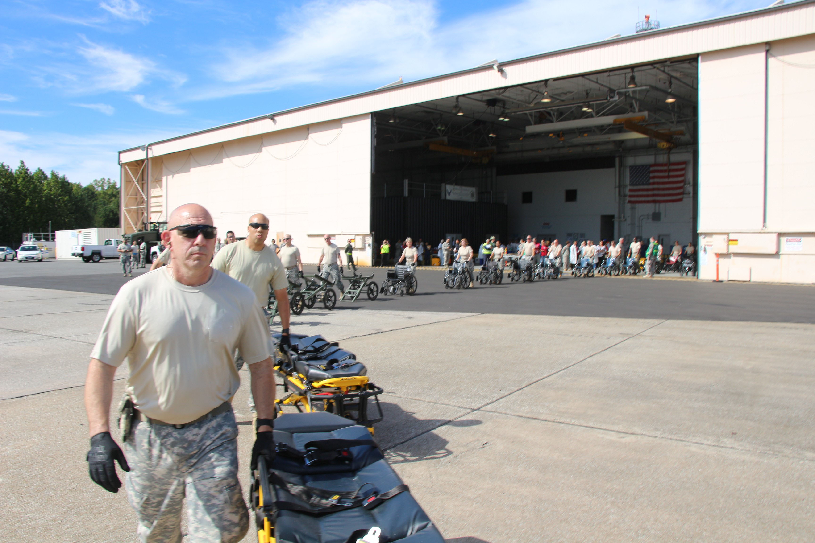 Specialist Joseph Costa lead the formation of Georgia State Defense Force soldiers lined up for offloading evacuees from the C-130H aircraft, who were transported to Dobbins Air Reserve Base, Marietta, Georgia from the U.S. Virgin Islands and Puerto Rico in the aftermath of Hurricane Maria, Oct. 1, 2017. Georgia State Defense Force photo by Maj. Vadim Timchenko